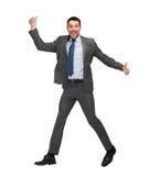 Hombre de negocios sonriente que salta y que muestra los pulgares para arriba Imagen de archivo libre de regalías