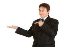 Hombre de negocios sonriente que señala el dedo en la mano vacía Fotos de archivo libres de regalías