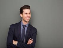 Hombre de negocios sonriente que se coloca con los brazos cruzados Imágenes de archivo libres de regalías