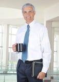 Hombre de negocios sonriente que se coloca en la configuración de la oficina Imagen de archivo