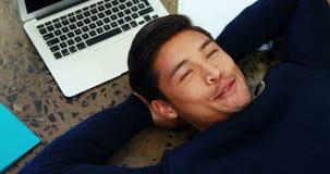 Hombre de negocios sonriente que se relaja en el piso 4k almacen de video