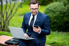 Hombre de negocios sonriente que se sienta en banco con el ordenador portátil y el teléfono móvil imágenes de archivo libres de regalías