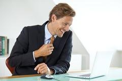 Hombre de negocios sonriente que se sienta en el escritorio fotografía de archivo