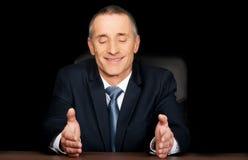 Hombre de negocios sonriente que se sienta en el escritorio Imagen de archivo