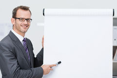 Hombre de negocios sonriente que señala a un flipchart en blanco Fotografía de archivo libre de regalías