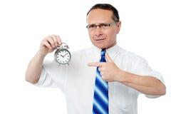 Hombre de negocios sonriente que sostiene un despertador Imagen de archivo libre de regalías