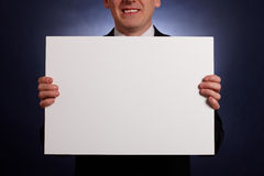 Hombre de negocios sonriente que sostiene una tarjeta en blanco grande Fotos de archivo libres de regalías