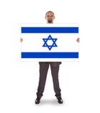 Hombre de negocios sonriente que sostiene una tarjeta grande, bandera de Israel Fotografía de archivo