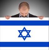 Hombre de negocios sonriente que sostiene una tarjeta grande, bandera de Israel Imágenes de archivo libres de regalías