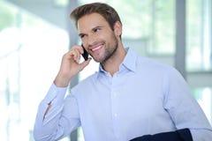 Hombre de negocios sonriente que tiene llamada de teléfono - hombre de negocios acertado - camisa azul Fotos de archivo libres de regalías