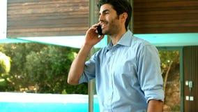Hombre de negocios sonriente que tiene una llamada de teléfono almacen de metraje de vídeo