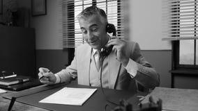 Hombre de negocios sonriente que trabaja en el escritorio de oficina almacen de metraje de vídeo