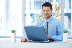 Hombre de negocios sonriente que trabaja en la computadora portátil Imagenes de archivo