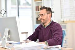 Hombre de negocios sonriente que trabaja en la oficina Fotos de archivo libres de regalías
