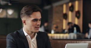 Hombre de negocios sonriente que usa el ordenador portátil que se sienta en la tabla del café almacen de metraje de vídeo