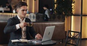 Hombre de negocios sonriente que usa el ordenador portátil que se sienta en la tabla del café metrajes