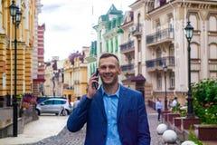 Hombre de negocios sonriente que usa el teléfono en ciudad foto de archivo libre de regalías