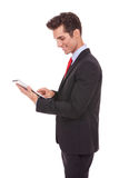 Hombre de negocios sonriente que usa su ordenador de la tablilla Fotos de archivo libres de regalías