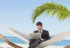 Hombre de negocios sonriente usando el ordenador portátil y el sentarse en hamaca Imagenes de archivo