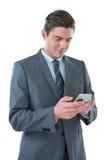 Hombre de negocios sonriente usando su teléfono Imagen de archivo libre de regalías