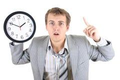 Hombre de negocios sorprendente en el juego gris que sostiene un reloj Foto de archivo libre de regalías