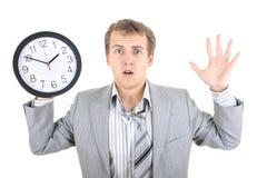 Hombre de negocios sorprendente en el juego gris que sostiene un reloj Imagen de archivo libre de regalías