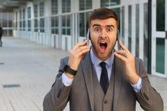 Hombre de negocios sorprendido con dos teléfonos móviles fotografía de archivo