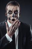 Hombre de negocios sorprendido con un esqueleto del maquillaje foto de archivo