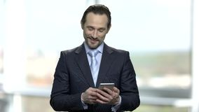 Hombre de negocios sorprendido que mira su smartphone metrajes