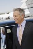 Hombre de negocios Standing By Car en el campo de aviación Fotos de archivo