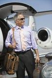 Hombre de negocios Standing With Luggage en el campo de aviación fotografía de archivo