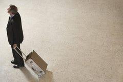 Hombre de negocios Standing With Suitcase en pasillo Fotos de archivo