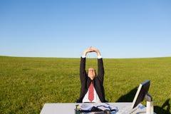 Hombre de negocios Stretching At Desk en campo herboso contra el cielo Imagenes de archivo