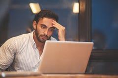 Hombre de negocios subrayado con el pensamiento del ordenador portátil imagenes de archivo
