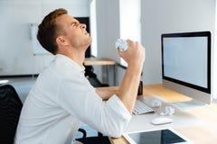 Hombre de negocios subrayado enojado que se sienta y papel de arrugamiento en oficina Imagen de archivo libre de regalías