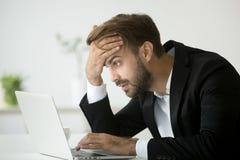 Hombre de negocios subrayado preocupante chocado por malas noticias en línea usando el la fotos de archivo libres de regalías