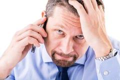 Hombre de negocios subrayado que hace una llamada de teléfono Imagenes de archivo