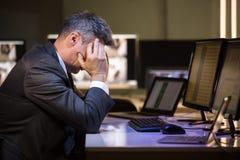 Hombre de negocios subrayado que se sienta en oficina foto de archivo libre de regalías