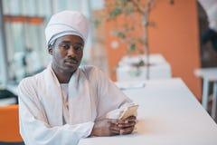 Hombre de negocios sudanés en equipo tradicional usando el teléfono móvil en oficina Imagen de archivo libre de regalías
