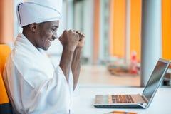Hombre de negocios sudanés en equipo tradicional usando el teléfono móvil en oficina Fotos de archivo libres de regalías