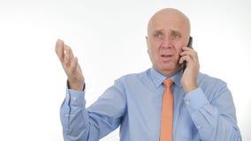 Hombre de negocios Talk Business del trastorno al teléfono móvil y hacer gestos de mano nerviosos fotografía de archivo