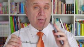 Hombre de negocios Talking Keeping Cellphone disponible y que gesticula con las lentes almacen de video