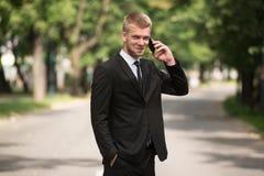 Hombre de negocios Talking On Telephone al aire libre en parque Fotos de archivo libres de regalías