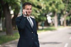 Hombre de negocios Talking On Telephone al aire libre en parque Imagen de archivo libre de regalías