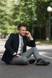 Hombre de negocios Talking On Telephone al aire libre en parque Fotografía de archivo