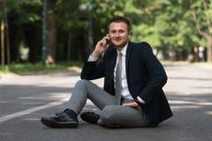 Hombre de negocios Talking On Telephone al aire libre en parque Imágenes de archivo libres de regalías