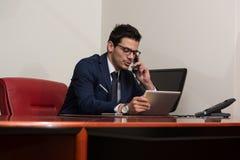 Hombre de negocios Talking On Telephone y ordenador con Imagen de archivo
