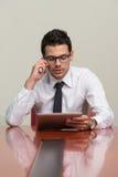 Hombre de negocios Talking On Telephone y tableta con Imagenes de archivo