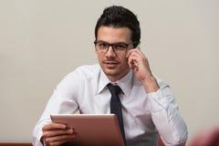 Hombre de negocios Talking On Telephone y tableta con Fotos de archivo