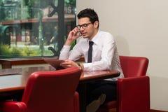 Hombre de negocios Talking On Telephone y tableta con Fotografía de archivo libre de regalías